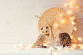 Christmas home decoration with lights on  white wooden background.