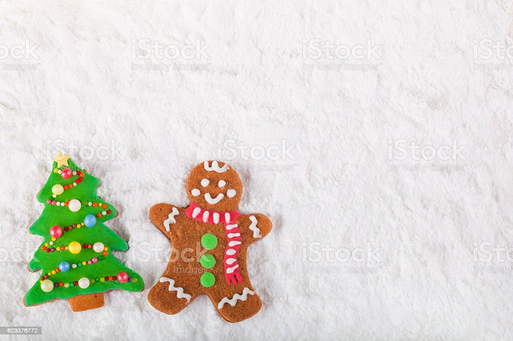 Christmas homemade gingerbread cookie man and tree on snow stock photo