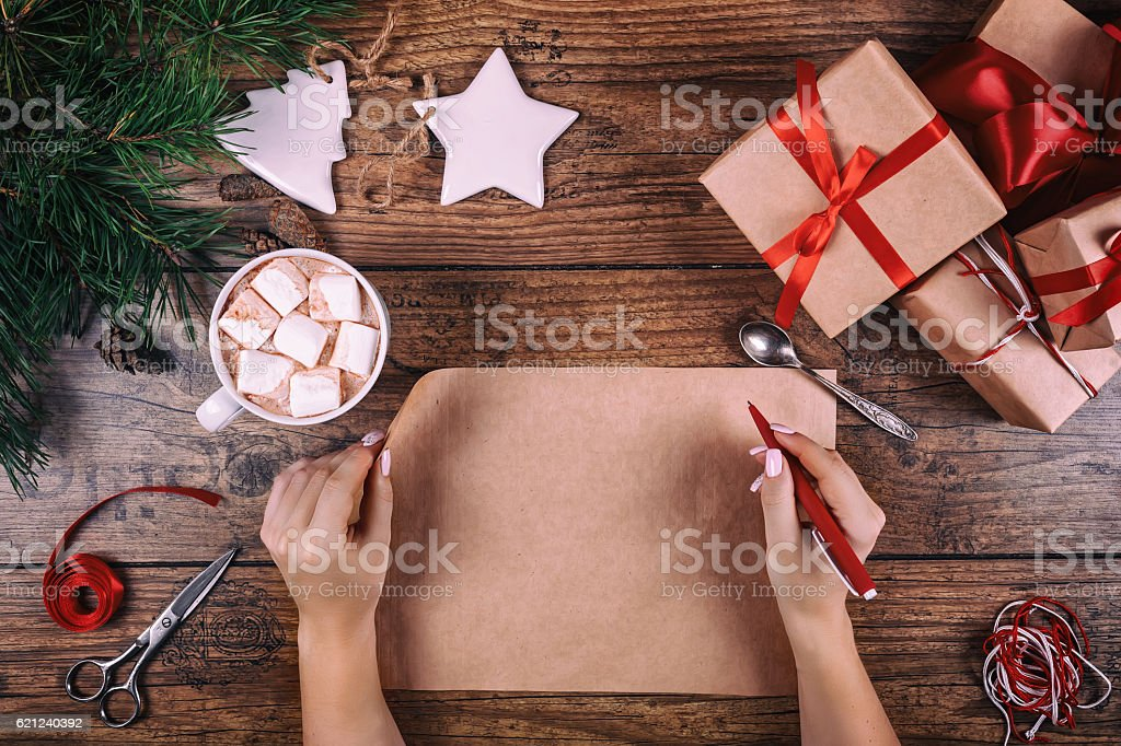 Christmas letter writing on paper on wooden background with decorations. stock photo