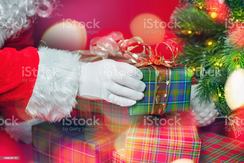 Christmas light and inspiration with Santa Claus putting gift box stock photo