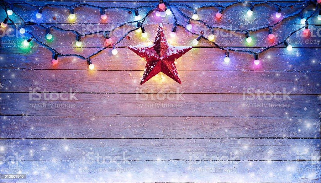 Christmas Lights And Star Hanging On Snowy Plank stock photo