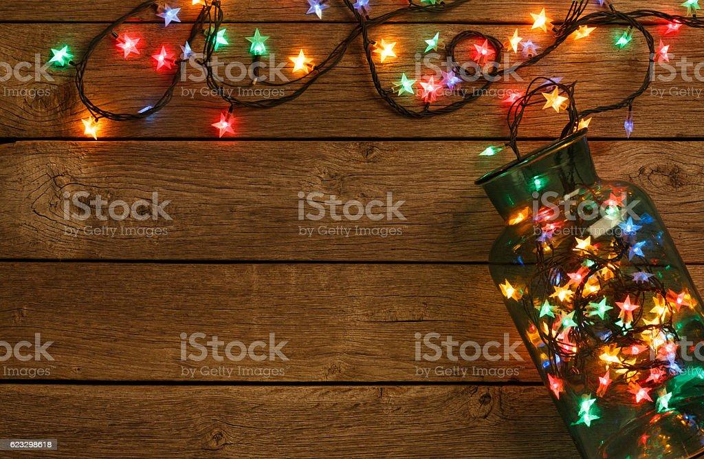 christmas lights border on wood background stock photo