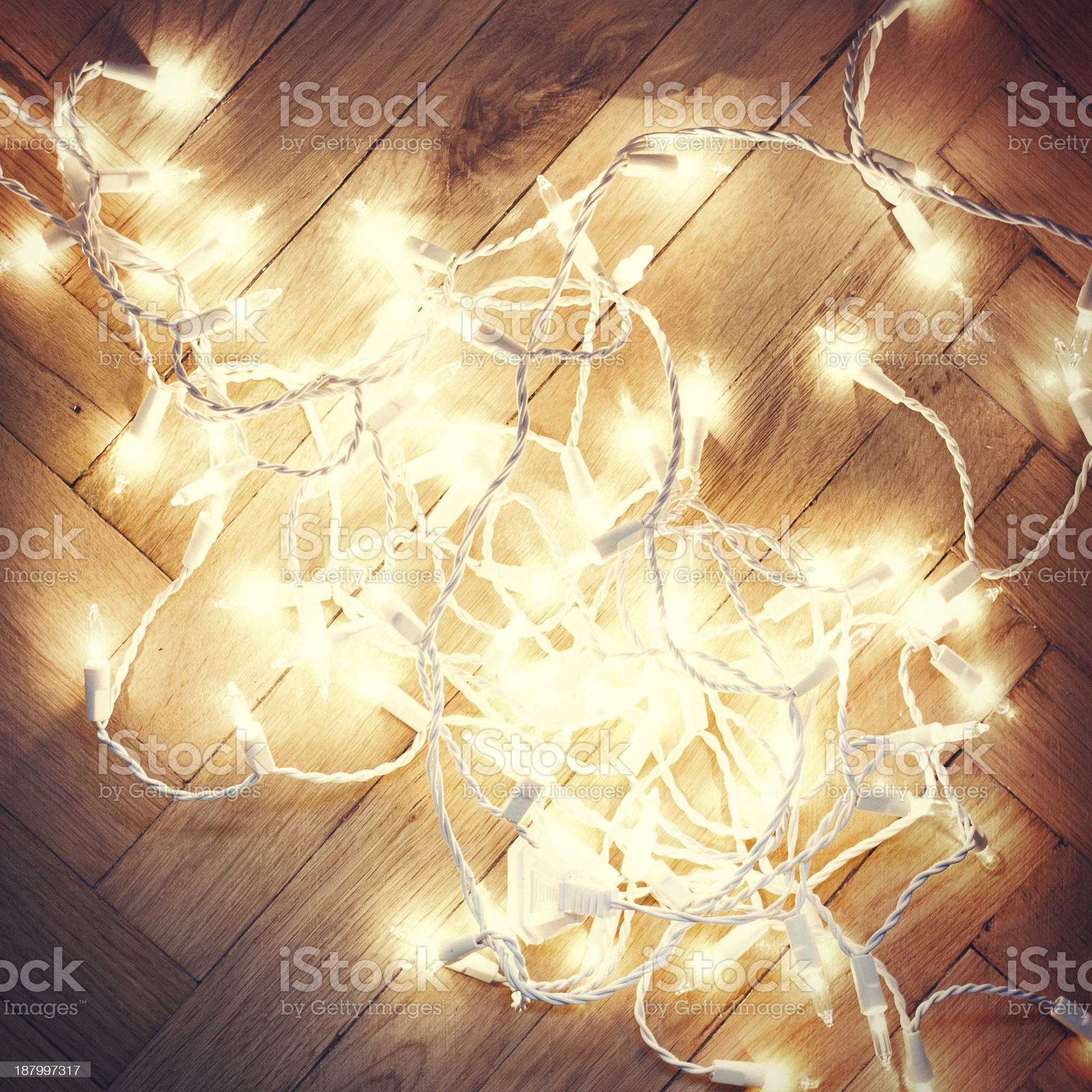 Christmas lights garland on a old antique wooden parquet floor, royalty-free stock photo