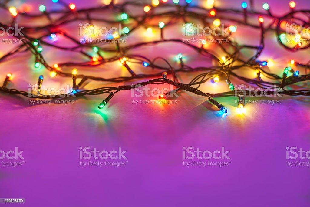 Christmas lights on dark pink background stock photo