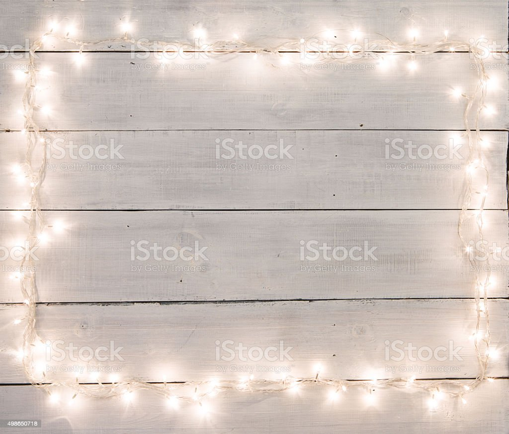 Christmas lights on white painted wooden background with copy sp stock photo