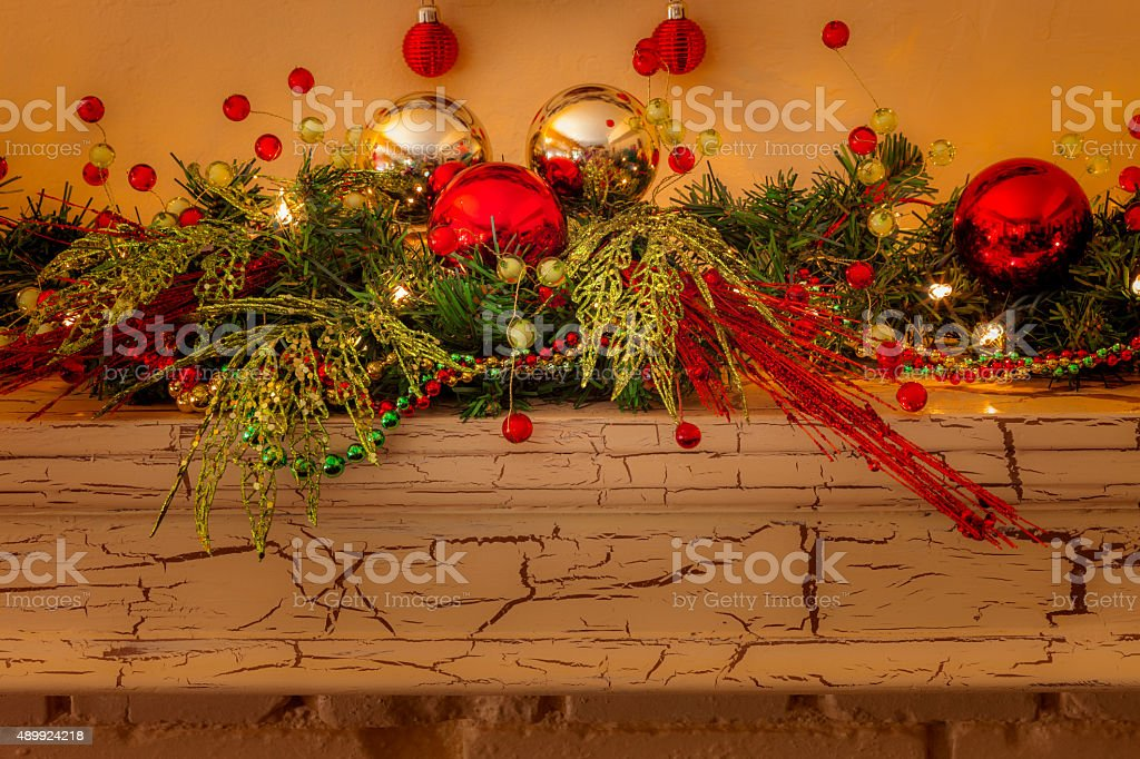 Christmas mantelpiece with garland,lights, red and gold bulbs (P) stock photo