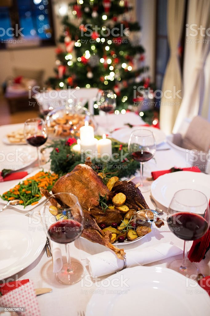Christmas meal laid on table in decorated dining room. Roasted turkey...