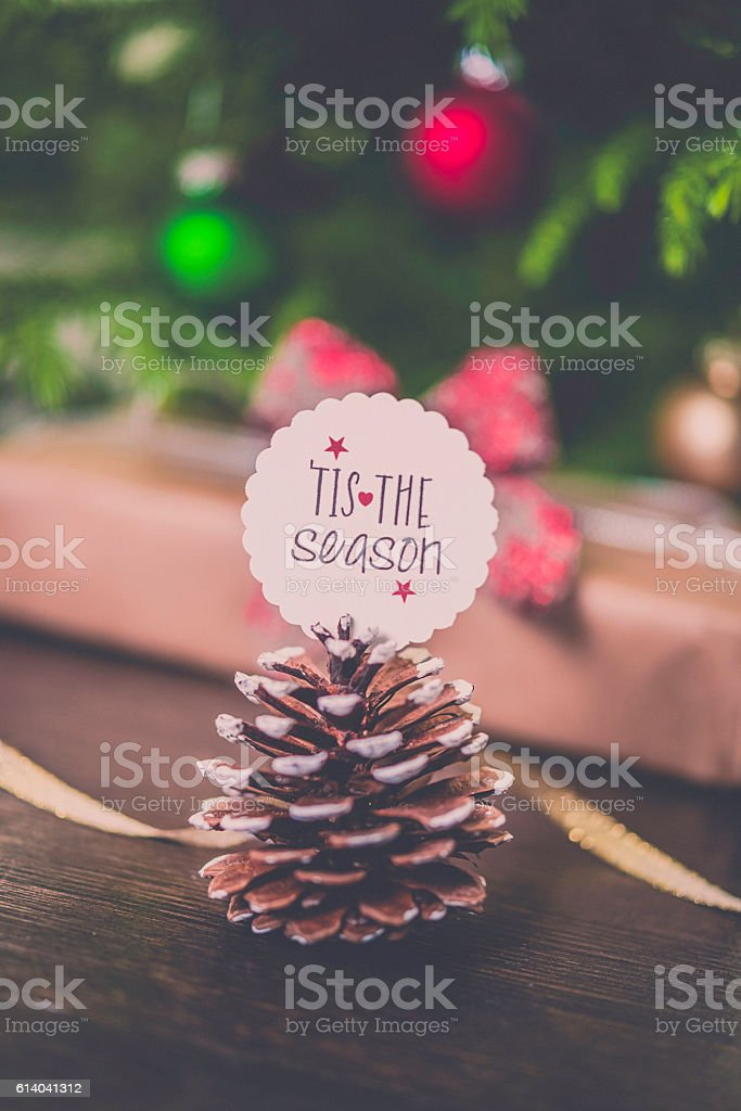 Christmas message with pinecone, gift, ribbon and decorations. stock photo