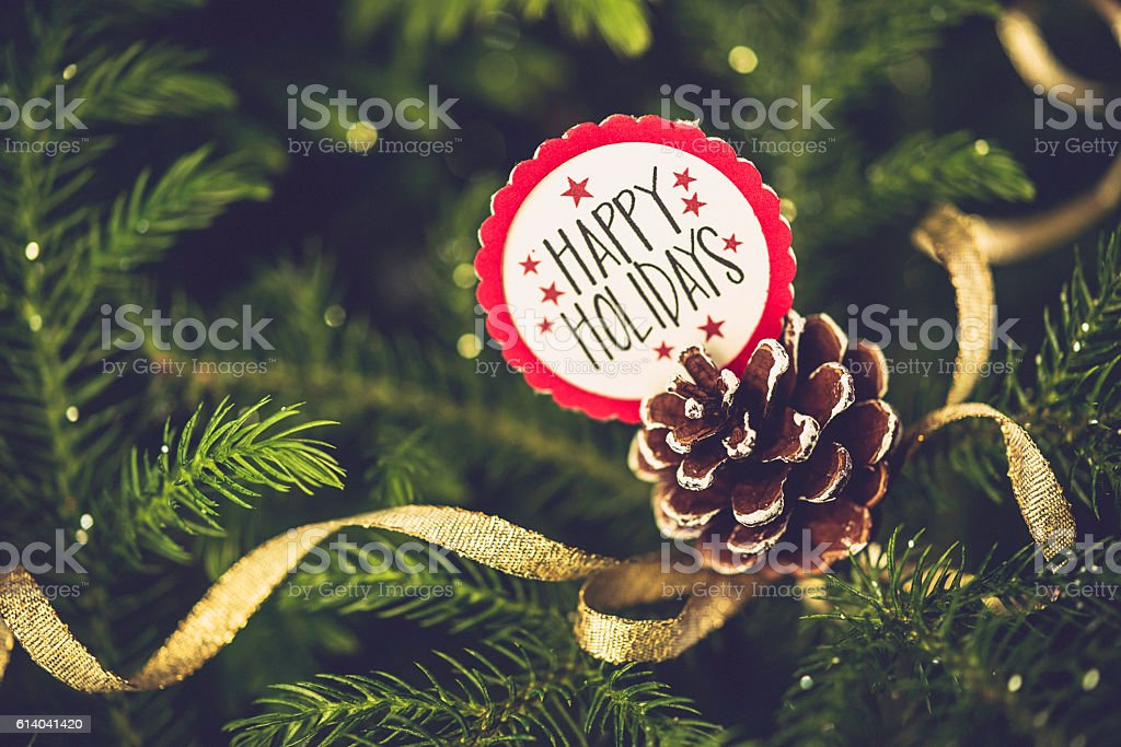 Christmas message with pinecone on real Christmas tree. Happy Holidays stock photo