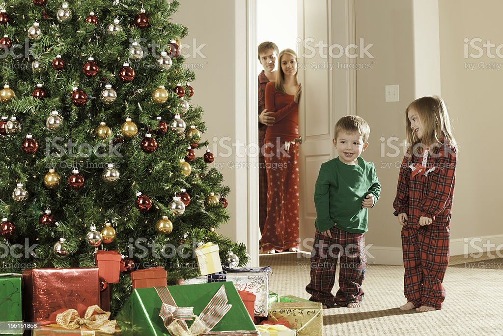Christmas morning excited children while parents watch royalty-free stock photo