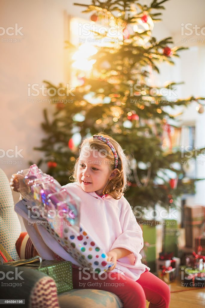 Christmas morning, little girl in pajamas opening the gift stock photo