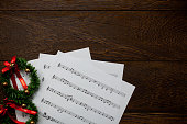 Christmas music note paper  with Christmas wreath on wooden.