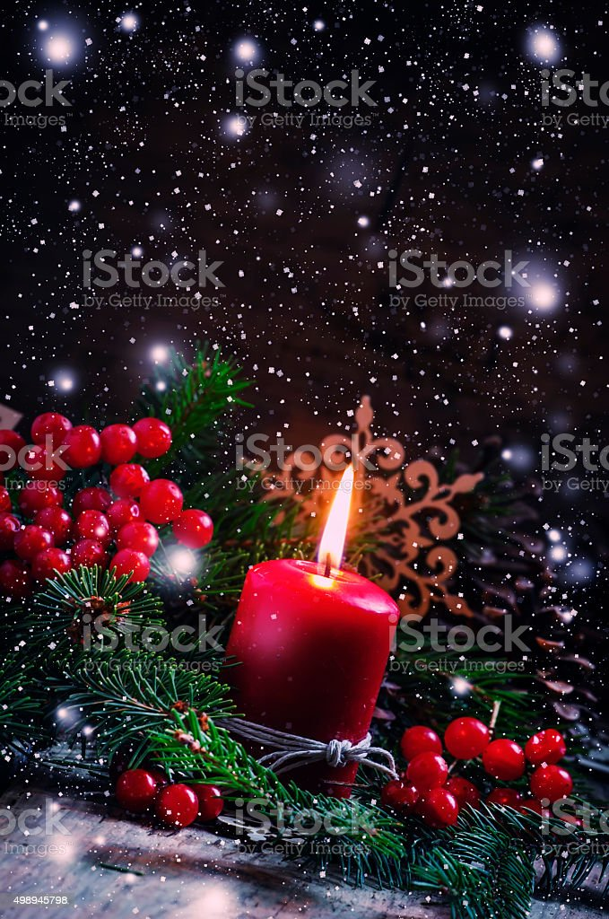 Christmas or New Year's dark composition with burning red candle stock photo