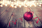 Christmas Ornament Baubles on Old Wood Background with Defocused Lights