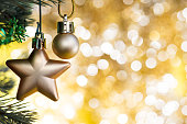 Christmas ornament decorate on fir tree with gold bokeh