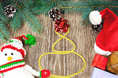 Christmas ornaments, fir branches and Christmas knitted snowman
