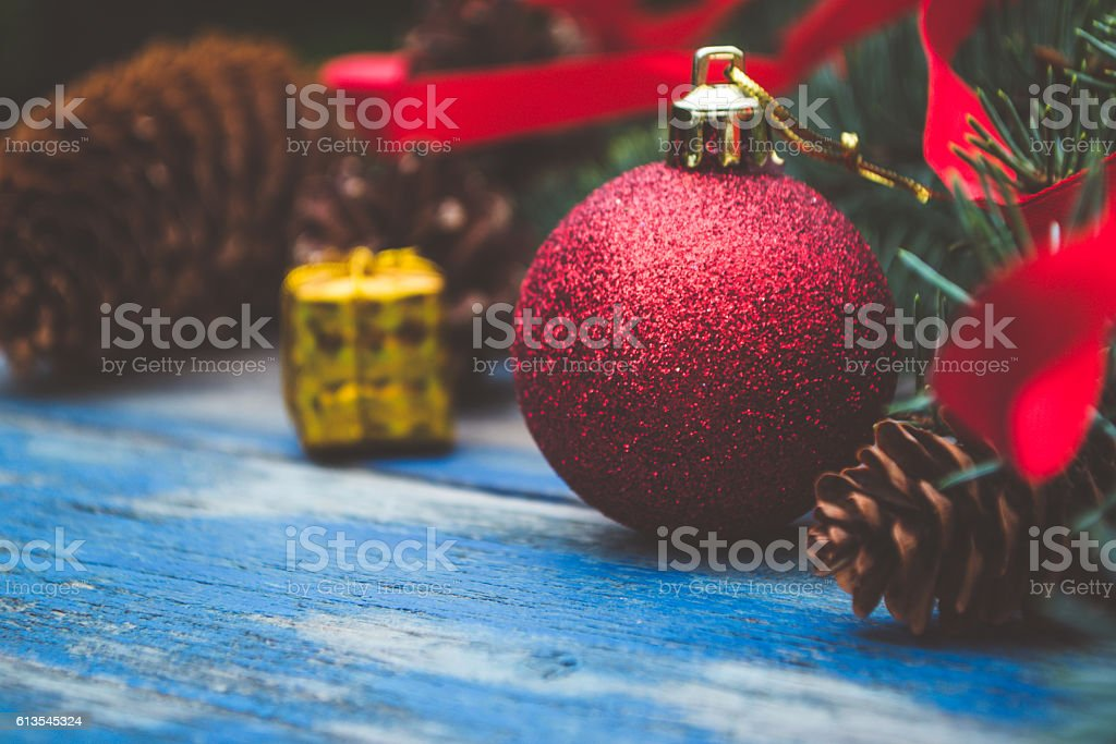 Christmas ornaments and branch of Christmas tree on old wooden table