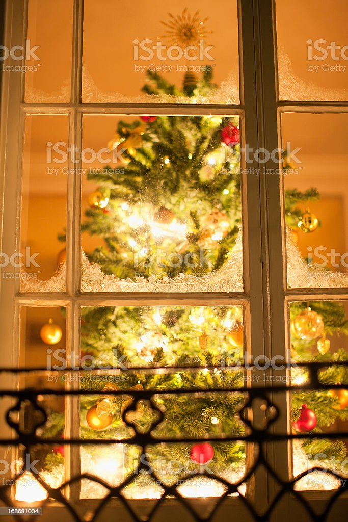 Christmas ornaments on tree behind window royalty-free stock photo