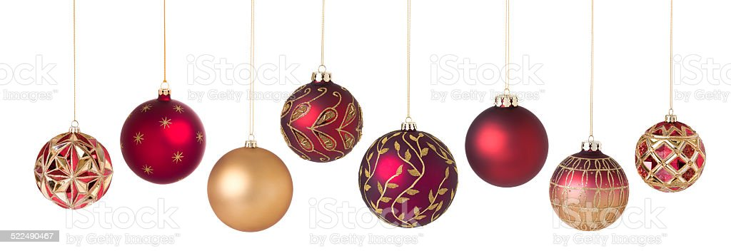 Christmas ornaments red gold in a row isolated on white stock photo