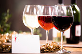 Christmas party with wine in glasses on rustic outdoor table.