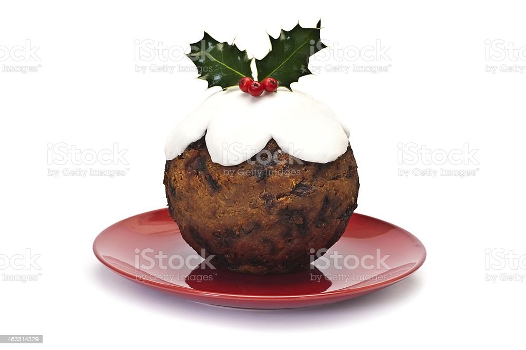 Christmas pudding on red plate with mistletoe decoration stock photo