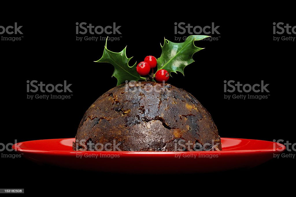 Christmas pudding with holly isolated on black stock photo