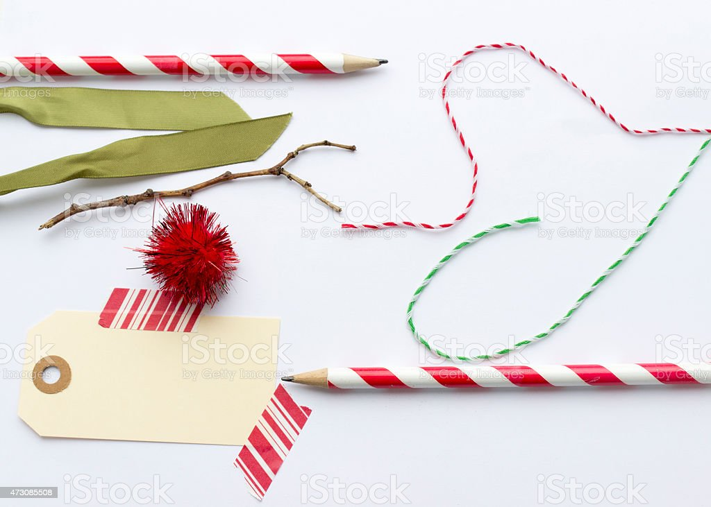 Christmas ribbons, label, string, tape and pencils on white background. stock photo