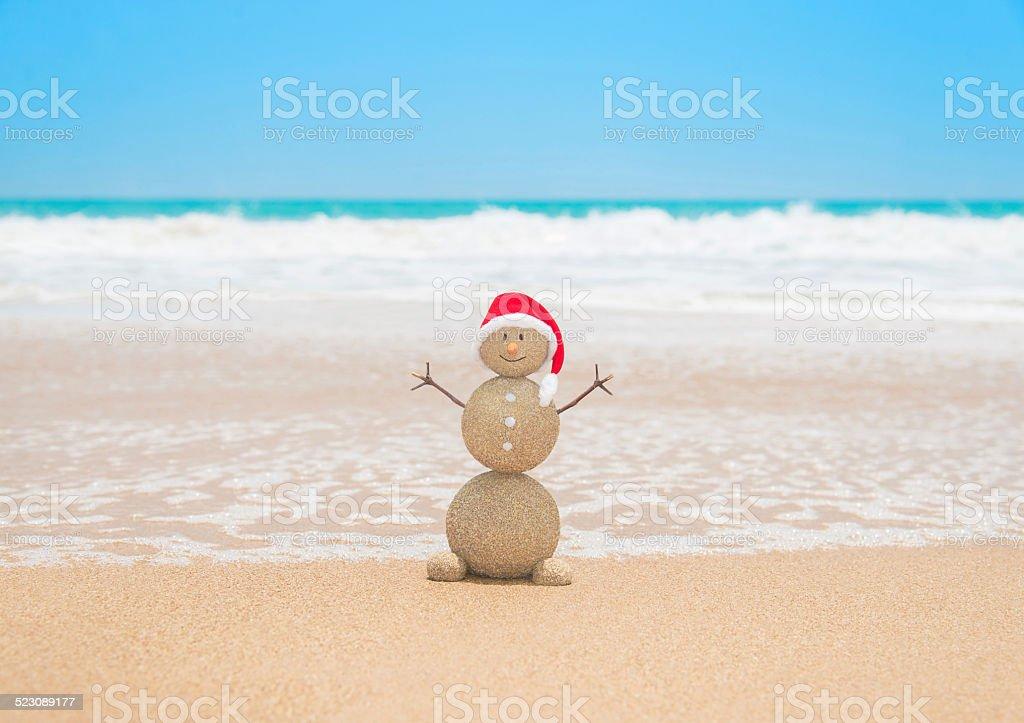 Christmas sandy snowman in santa hat at tropical beach stock photo
