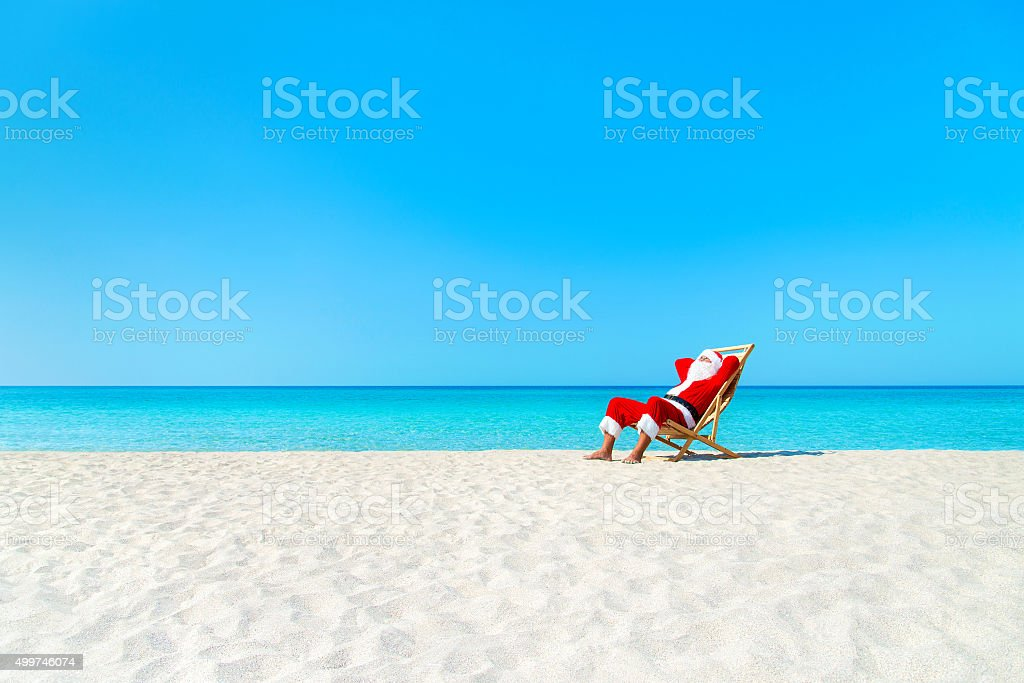 Christmas Santa Claus resting on deckchair at ocean sandy beach stock photo