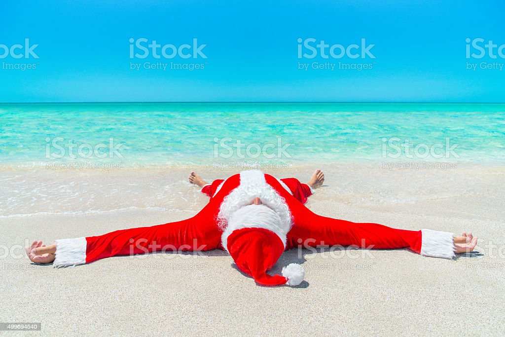 Christmas Santa Claus take pleasure sunbathing at tropical ocean stock photo