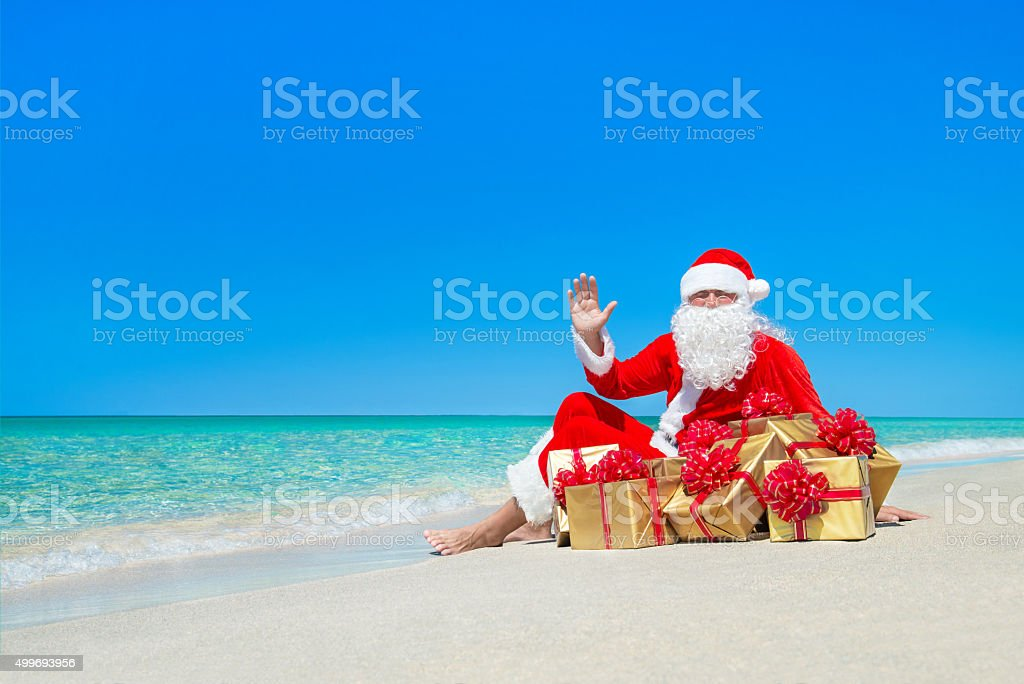 Christmas Santa Claus with gift boxes resting at ocean beach stock photo