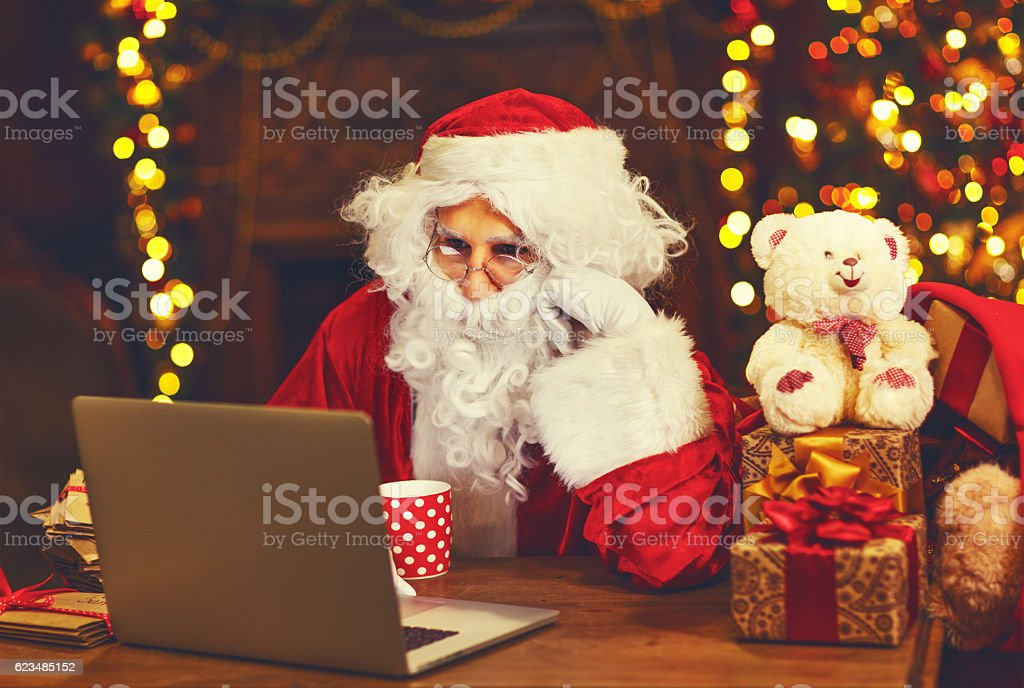 Christmas. Santa Claus with laptop reading letter stock photo