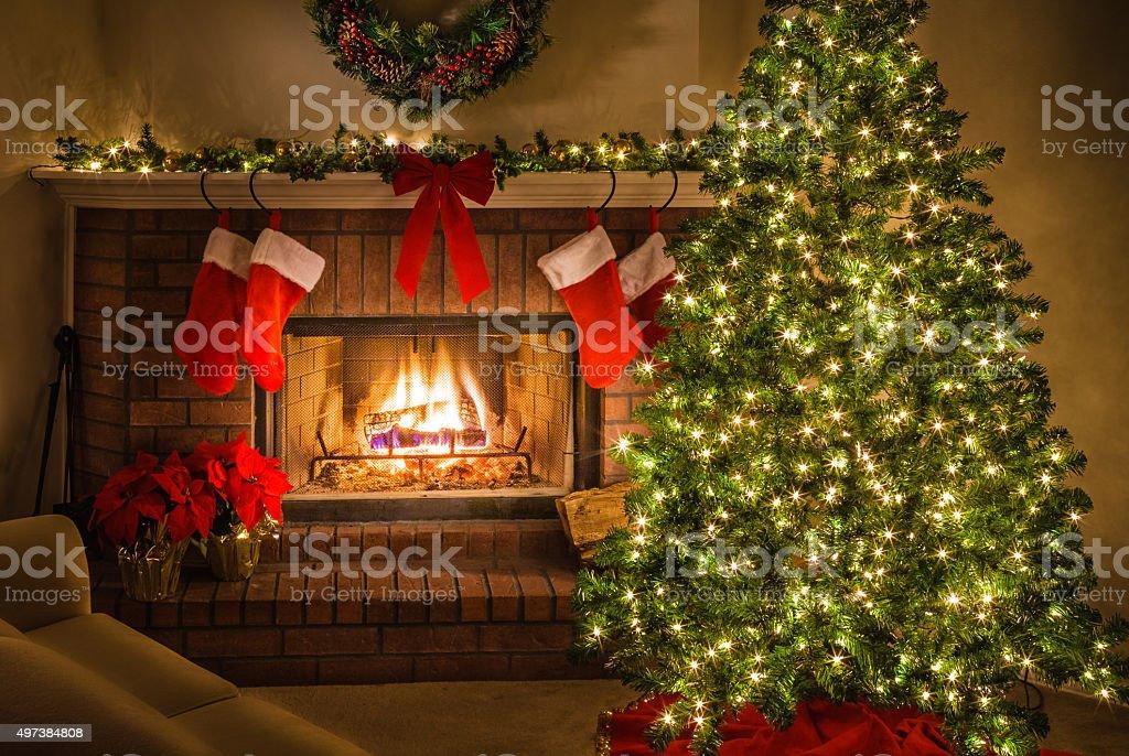 Christmas scene, blazing fireplace, decorated tree, stockings, cozy living room stock photo