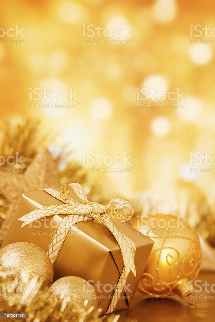 Christmas scene with gold baubles and gift, gold background royalty-free stock photo