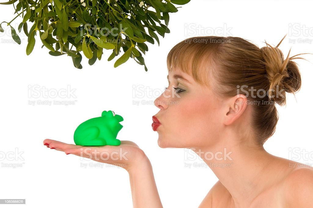 Christmas series - Woman kissing a frog under mistletoe royalty-free stock photo