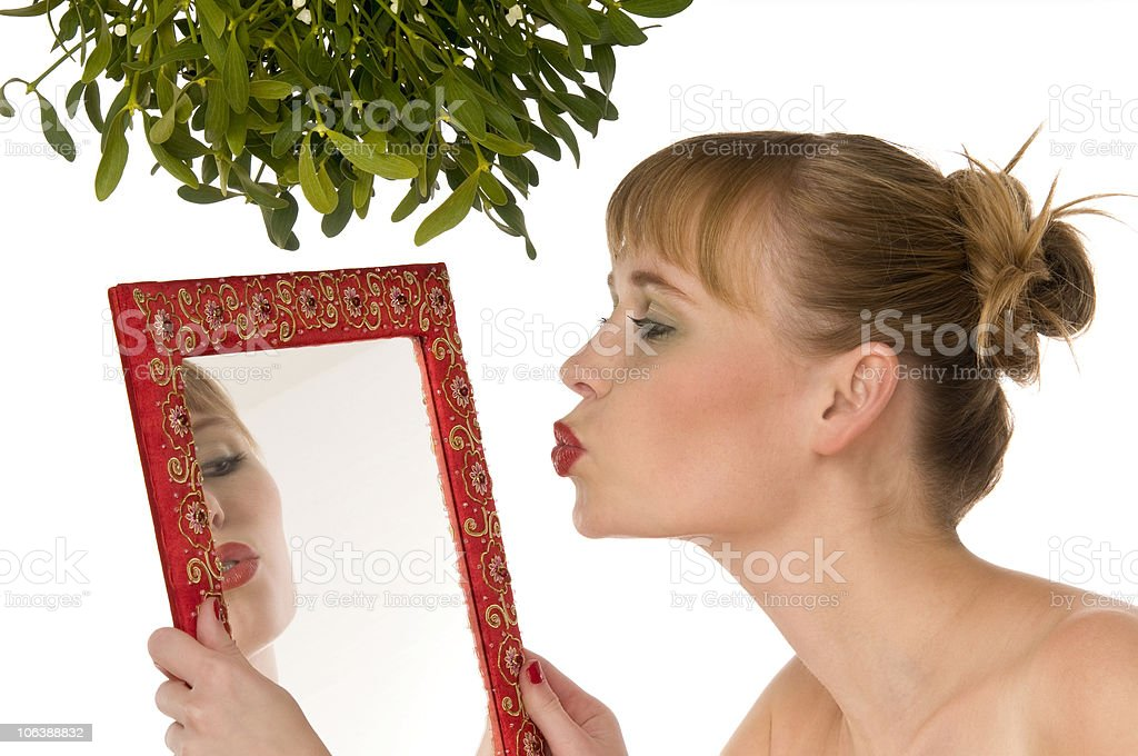Christmas series - Woman kissing herself in mirror under mistletoe stock photo