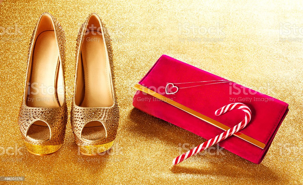 Christmas shopping. Gold heels,red bag,candy cane. stock photo