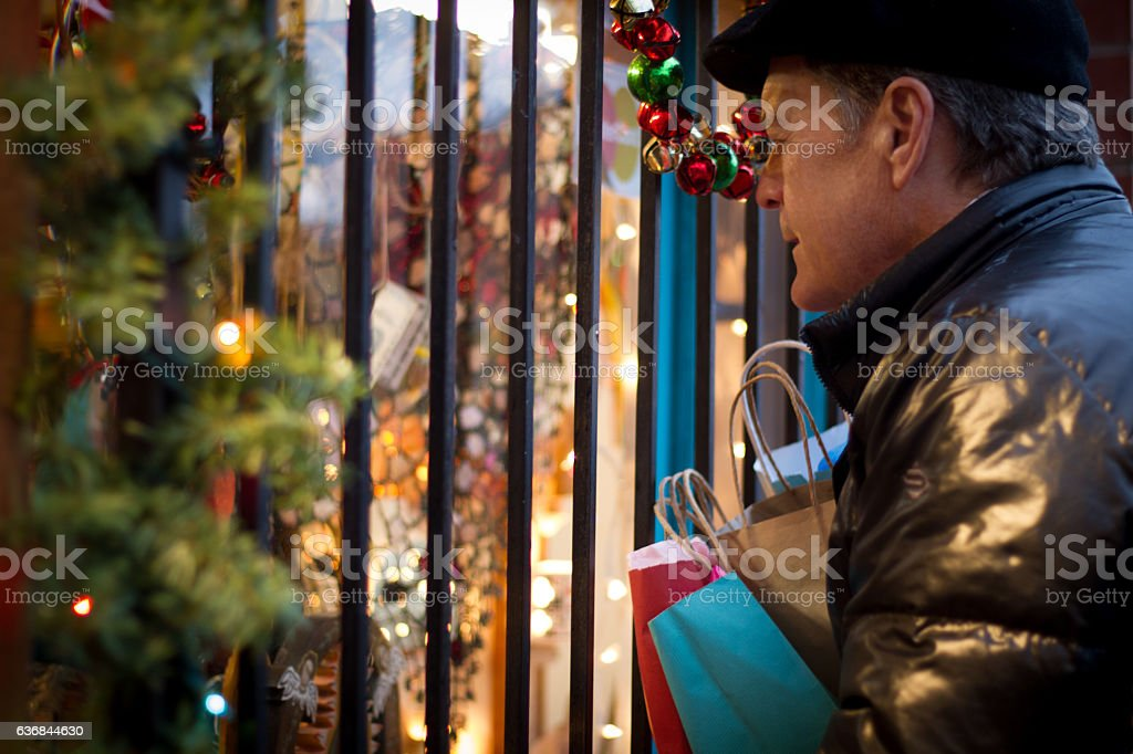 Christmas Shopping: Man with Shopping Bags Peers into Shop Window stock photo