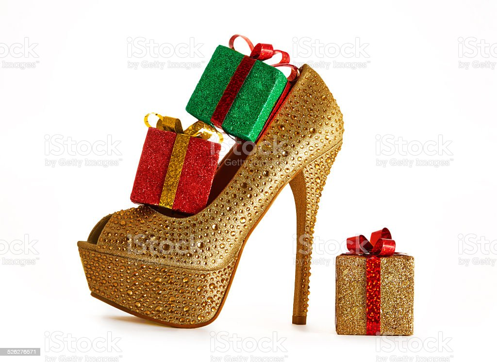 Christmas shopping.Sexy gold heel with presents. stock photo