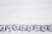 Christmas silver apples decoration  on wooden white background.