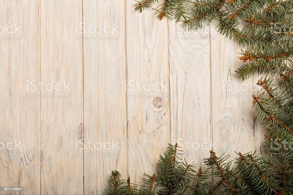 Christmas spruce branches with cones on white wooden Board. stock photo