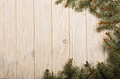 Christmas spruce branches with cones on white wooden Board.