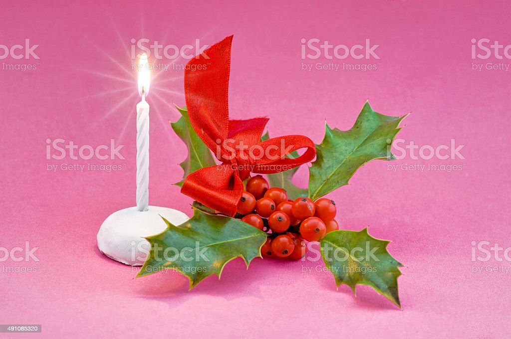 Christmas still life with candle and holly stock photo