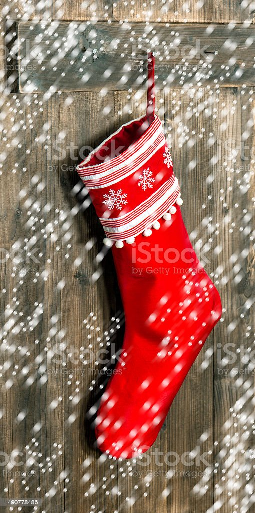Christmas stocking. Red sock with snowflakes  and falling snow stock photo