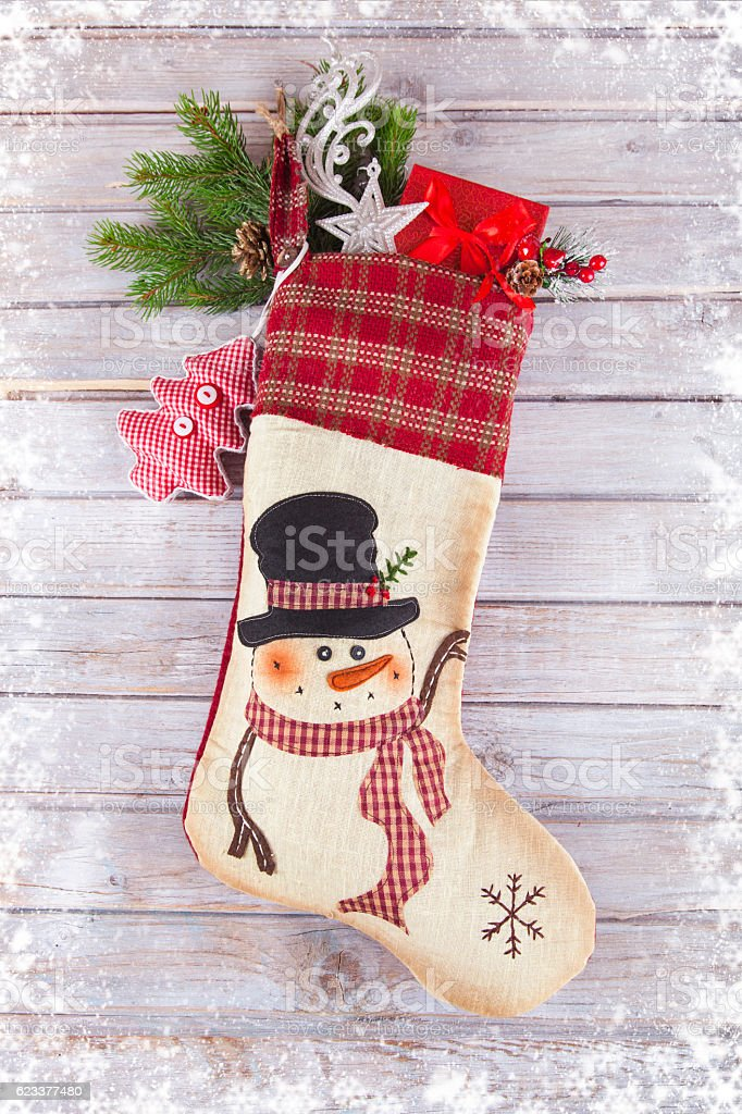 Christmas stocking Sock with Santa gifts on wooden background stock photo