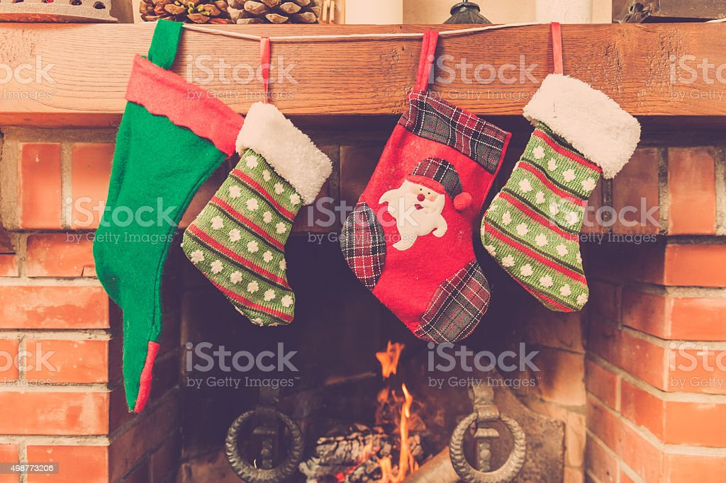 Christmas stockings hanging above a fireplace stock photo