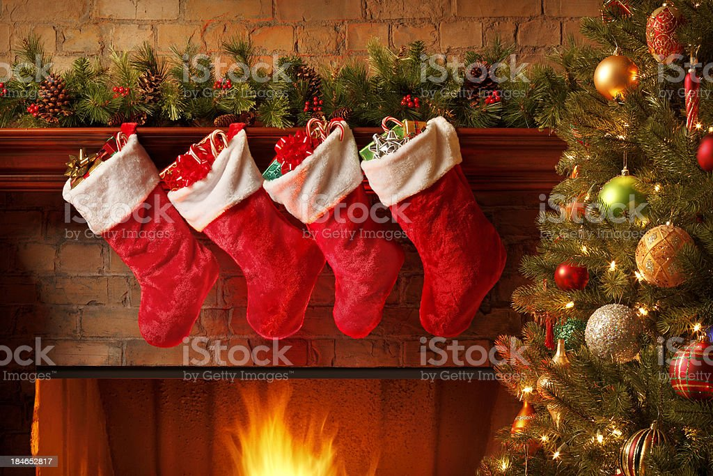 Christmas stockings hanging from a mantelpiece above glowing fireplace stock photo