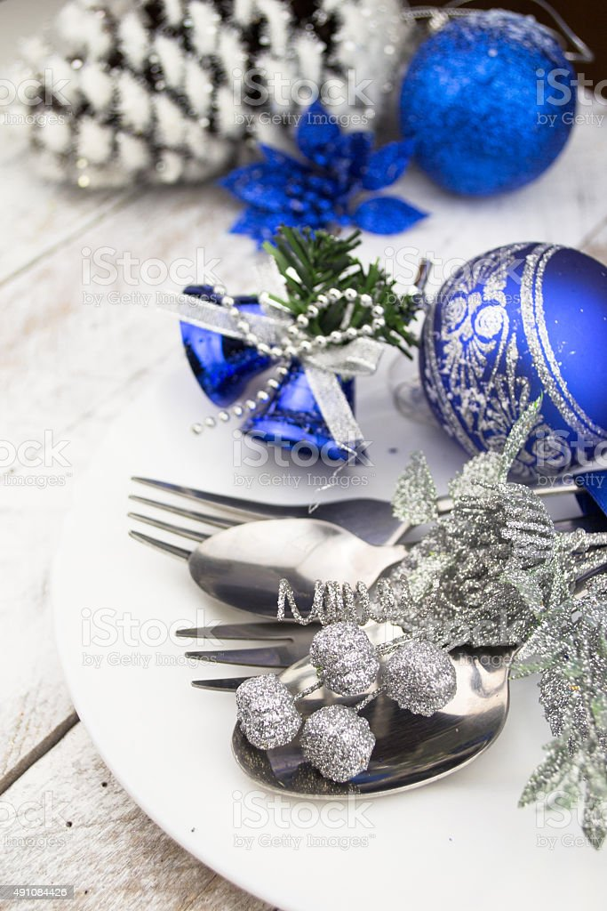 Christmas table setting in silver and blue tone on wood stock photo