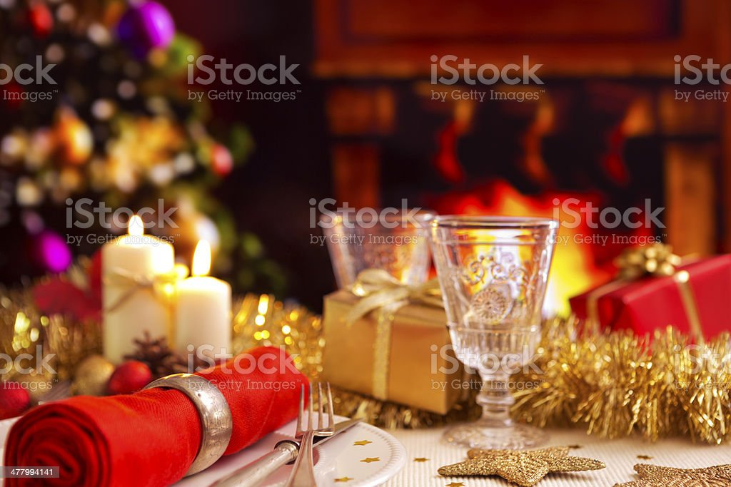 Christmas table with fireplace and Christmas tree in the background royalty-free stock photo