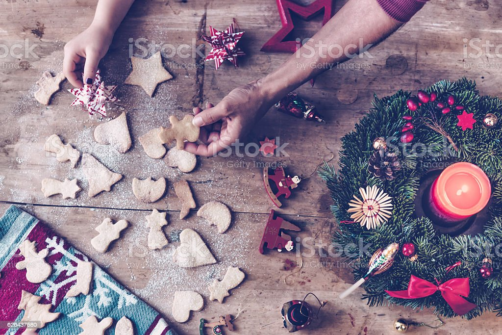 christmas table with hands holding selfmade cookies and Advent wreath stock photo